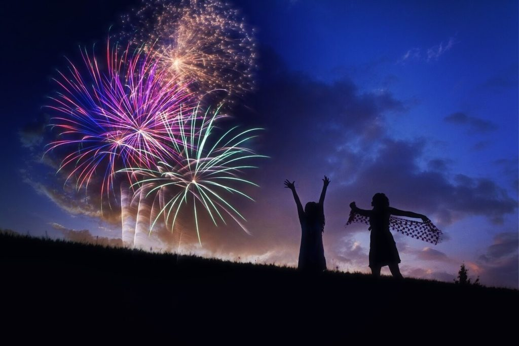 Fireworks with two children in silhouette.