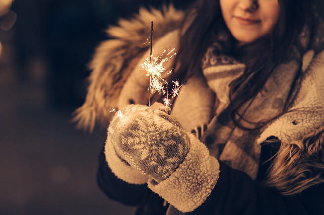Girl in a coat holding sparkles.